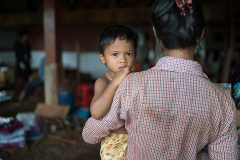 A mother holds her child at the longitudinal study health data collection site in Lung Kung village, Lung Kung commune in Ratanakiri on June 12, 2018.