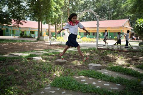 A girl runs jumps from step to step during recess at Russey Chroy Primary School in Sa'ang district, Kandal province