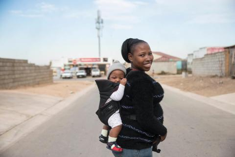 Abongile Mpati poses with her baby Linothando (4 months) in a street near her house