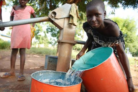 A girl pours water from one bucket into another after getting water from a handpump in the village of Moglaa, Ghana