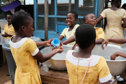 Students washing their hands before purchasing snacks from vendors at Blessed Clementina Roman Catholic School in Ashaiman, Ghana