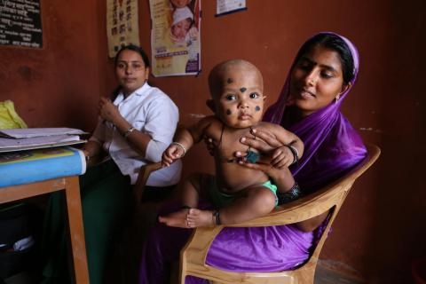 Young mother awaits immunization with her baby, in a village in Raipur area.