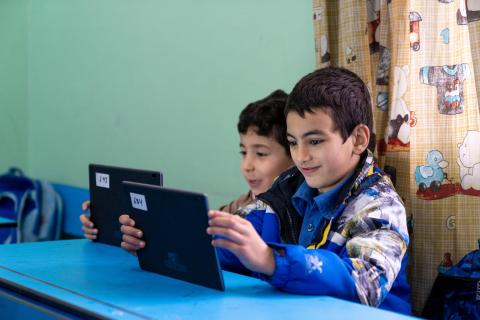 Two young boys at school learning from an IPAD