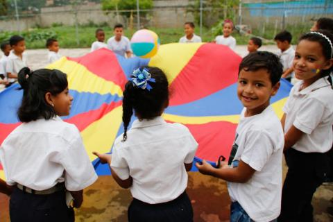 Children participate in recreational activities on the school's sports field of Negro Primero 1 school in Caucaguita, Miranda