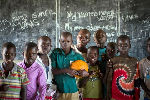 Pupils write their names on a blackboard in in Arua District.