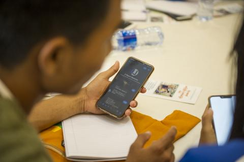 A young person uses his mobile phone to access U-Report app