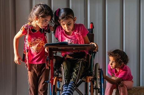 A girl in a wheelchair reads a book with her two friends