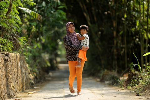Rita Iriati, carrying her 3-year-old daughter, Novita, walks on a road in the village of Kemalang in Klaten District, Central Java Province.