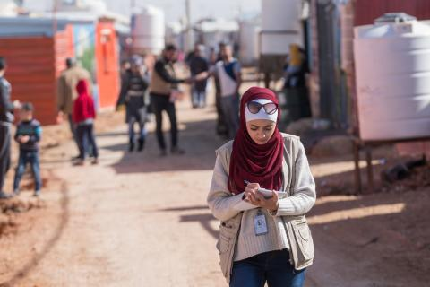 On 18 January 2017 in Jordan, Hala Abu Ghoush, writes in a notebook as she walks in the Za'atari camp for Syrian refugees, in Mafraq Governorate, near the Syrian border.