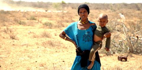 A mother carries her child as she walks in the drought-stricken Badanrero village in Moyale, Marsabit County, Kenya