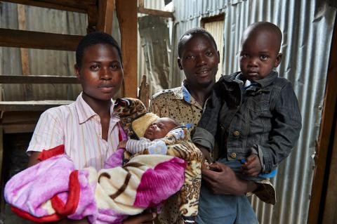 Martin and Maximila along with their two children stand outside their home in Mukuru, Nairobi, Kenya