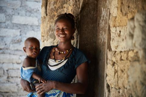 Fatima Kanu, holding her son, 13-month-old Menday Sesay, smiles outside a building in Manjaga Village in Bombali District