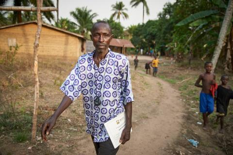 Community Health Worker (CHW) Brima Bangura, carrying health papers, walks through Maforay Village in Safroko Limba Chiefdom, Bombali District. Two boys are visible behind him. Mr. Bangura became a CHW in 2012 to help bring basic maternal and child health services closer to his village.