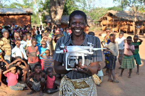 "Resident Rhoda Nkhambule holds a drone following a public demonstration of the technology to residents in Thipa vllage, Kasungu District, Malawi, Thursday 29 June 2017. ""I know how important vaccinations are to our children,"" says Rhoda, ""Medical staff tell us that children have to receive their vaccination on time, but our children can only receive vaccinations once a month because we are so far from the health centre. If they miss it, they have to wait for the following month, putting them at risk of catc"
