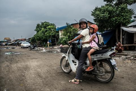 Social worker Phon Chanthorn (47) on a moto with her daughter Ung Srey Peou leaving their house in Daun Penh district, Phnom Penh, Cambodia.