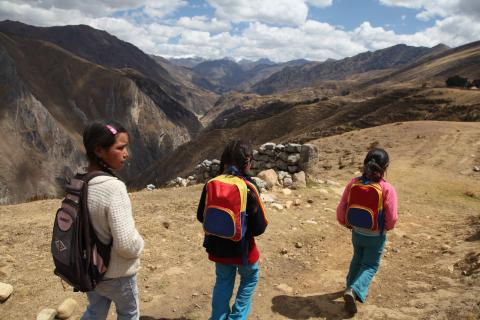 children walking by the mountains in Peru