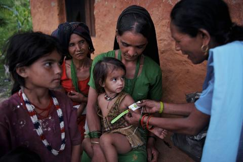 Community health volunteer using a MUAC bend to measure a child's malnutrition in Nepal.