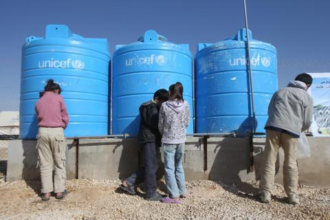 Children are filling up the water containers from the UNICEF water tanks in the Zaatari refugee camp.