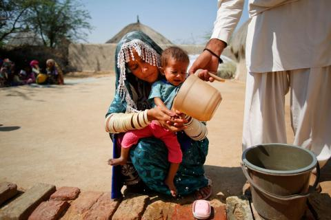 A nutrition assistant helps Lata (7 months) and her mother for washing hands at UNICEF supported CMAM site in Village Meghwar pro chelhar, Tharparker district, Sindh province, Pakistan