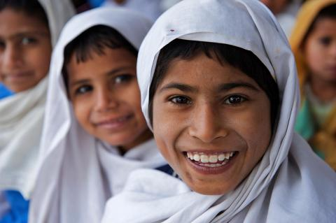 Children smile while attending school in a UNICEF-supported Temporary Learning Centre (TLC) in the village of Basti Bhaya in Rajanpur