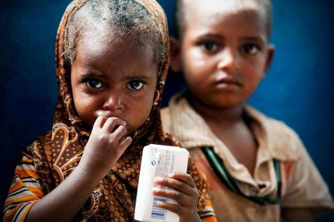 Two children eating food to treat malnutrition