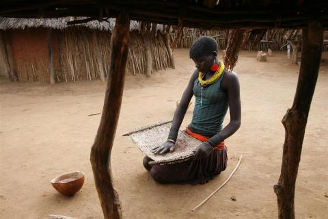A Karamojong girl cleans grains in her family compound in a 'manyatta' (semi-permanent village) near Kotido Town in the northern Kotido District.
