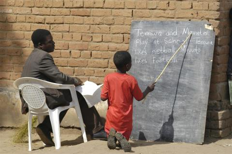 With his teacher seated beside him, a boy takes an English reading test kneeling in front of a blackboard that is propped against an outside wall at Chadza Primary School in a rural district near Lilongwe.
