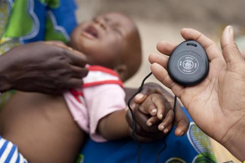 Community Health Volunteer Mariam Diarra times eight-month-old Gimbala Keita's breathing, using a WHO/UNICEF timer, during an outreach visit in Kabe Village in the western Kayes Region. The baby has pneumonia.