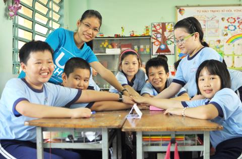 Upshift volunteer joins huddle of children in a school in vietnam