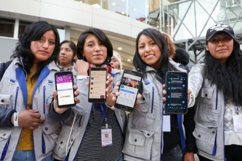 Young boys and girls in Bolivia showcasing phones with U-Report