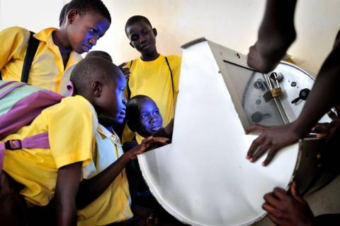 Young boys look at a digital monitor made of metal