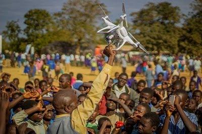 Drone being raised by a man in a crowd
