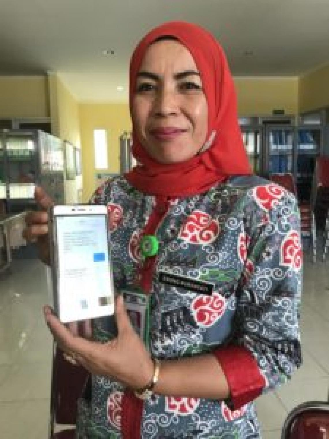 Ms. Enung Nurhayati holding a mobile phone