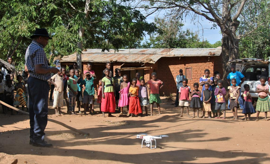 Chief Air Traffic Controller Steve Mkandawire (left), one of five Civil Aviation certified pilots, demonstrates a drone to residents in Thipa vllage, Kasungu District, Malawi