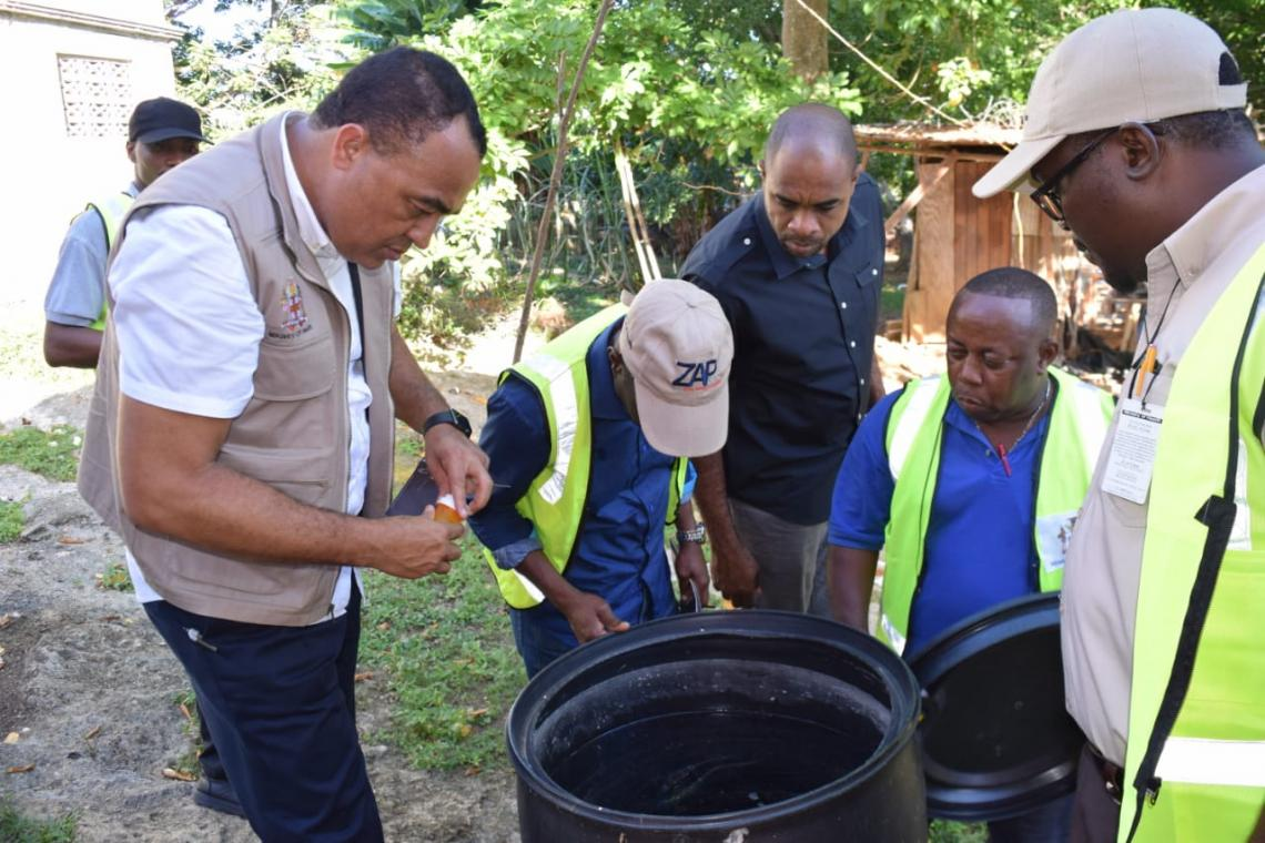 Minister of Health & Wellness Chris Tufton (in beige vest) looking into a drum (potential mosquito-breeding site).