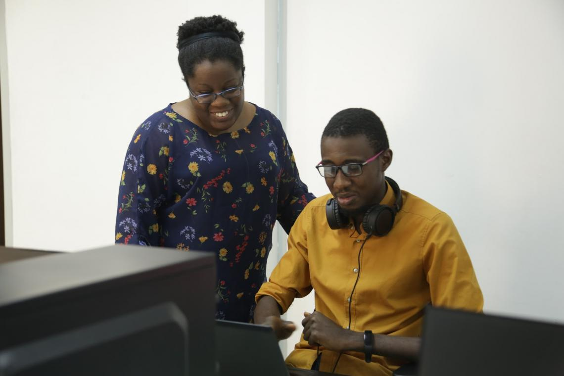 Judith Okonkwo, founder of Imisi 3D, working with a member of her team on a VR for education project.