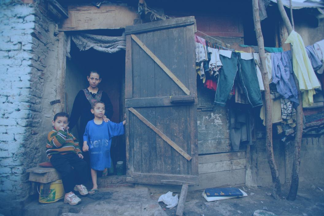 Family sitting outside home at urban slum area