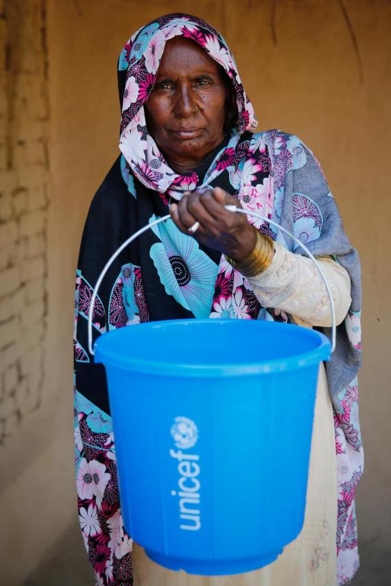Sattan Bibi (60) uses UNICEF provided bucket to store drinkable water in her house in the flood affected village Bohrra Ghulam Jahanian, Jhang district, Punjab province, Pakistan.