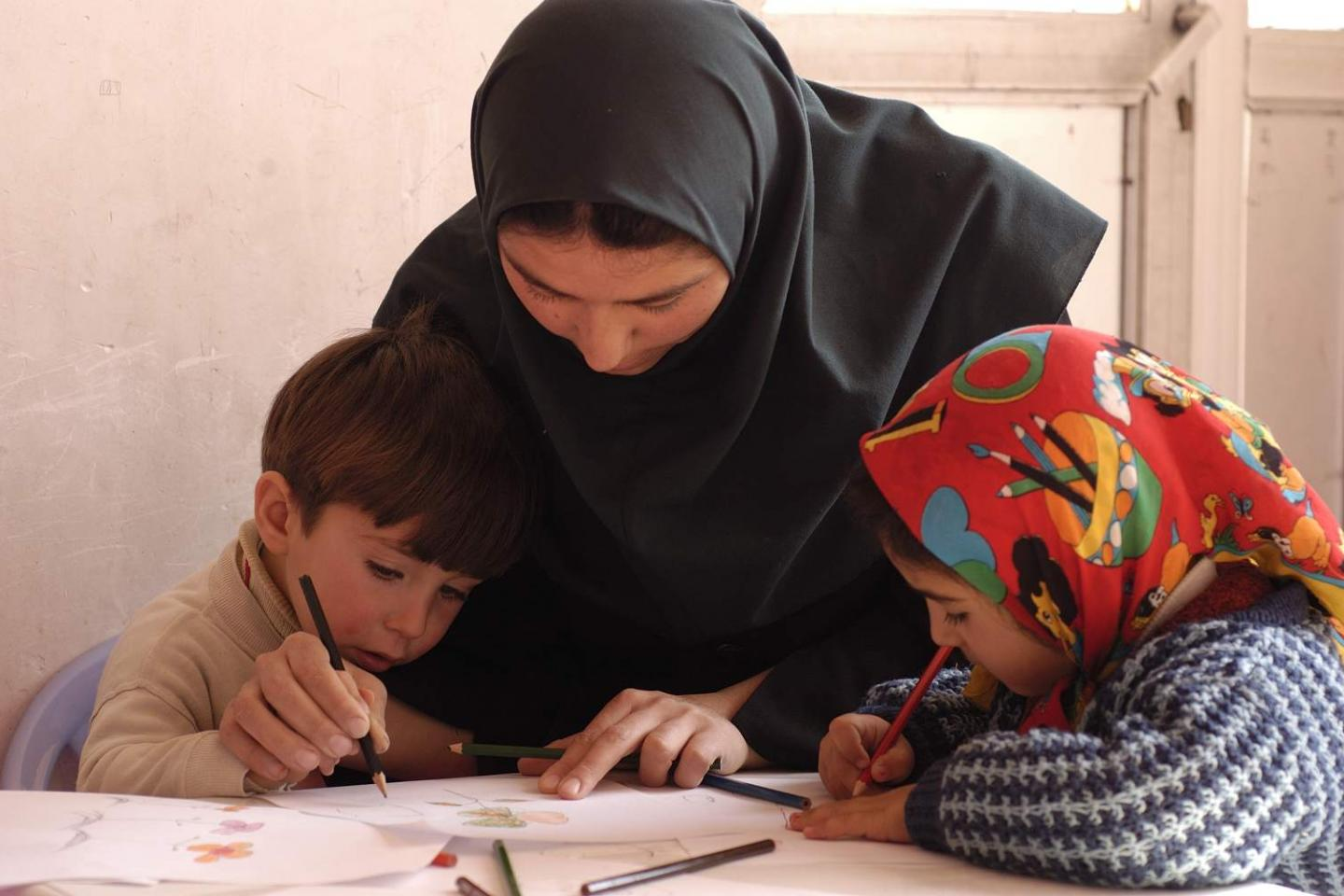 A teacher helps a child to write