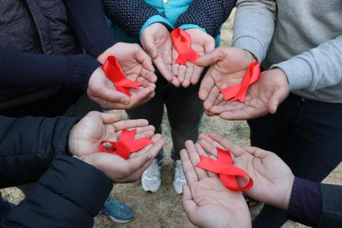 Children with red ribbon in hands