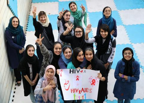 girls holding a banner against HIV/AIDS