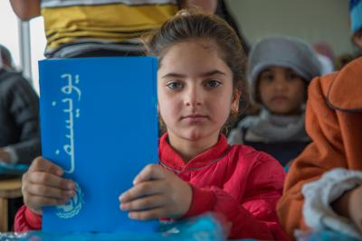 A girl sit in a classroom holding UNICEF copy book