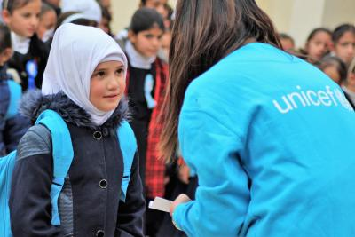 A UNICEF staff standing with a child during winterization distribution