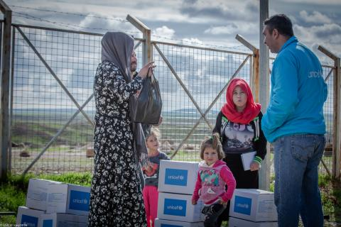 A UNICEF staff member speaks to a mother and her children, after they received winter clothes support.