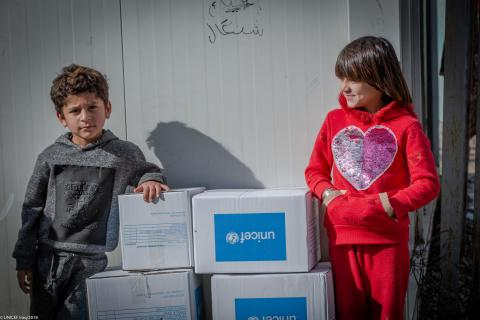 A brother and a sister are standing beside UNICEF kits