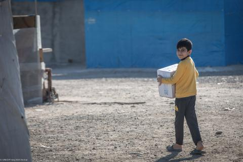 Ahmed from Mosul, 12 years old, lives in Baharka IDP camp in Erbil, Iraq, receiving his winter clothes box.