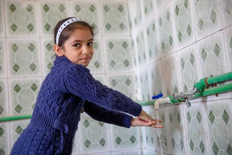 A girl washes her hands in Iraq