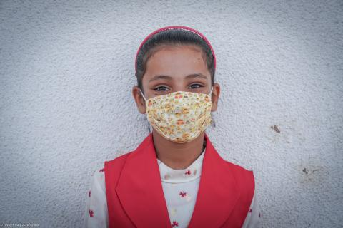A girl wearing a mask stands by a wall in Iraq