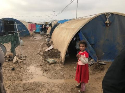 A young girl stands in front of her home in Airstrip camp, Iraq.