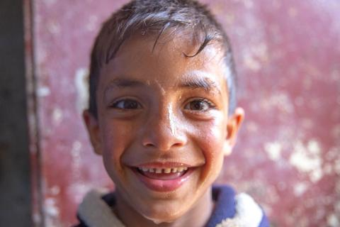 A boy smiles as he water flows from his face